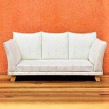 Weiße Couch auf Parkettboden vor orangener Wand