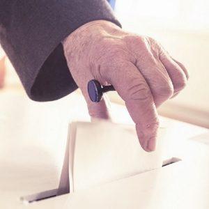Hand eines alten Mannes, der einen Wahlzettel in eine Wahlurne einwirft