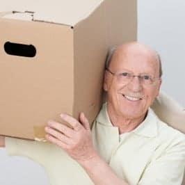 Aktiver Rentner trägt Umzugskarton