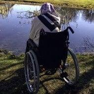 Frau mit Kopftuch im Rollstuhl