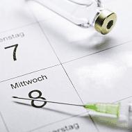 Spritze, die auf einem Kalender liegt