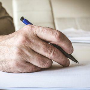 Hand eines alten Mannes mit blauem Kugelschreiber
