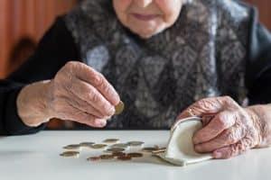 Eine alte Frau sitzt am Tisch und zählt Geldmünzen