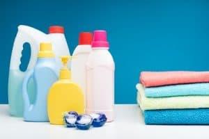 Waschmittel und ein Stapel Handtücher vor blauem Hintergrund