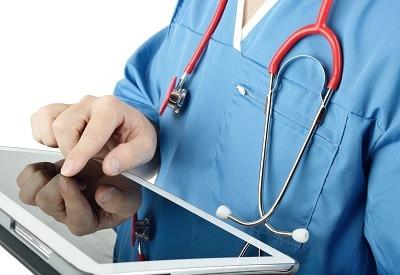 Arzt in blauem Kittel tippt mit dem Finger auf ein Notebook