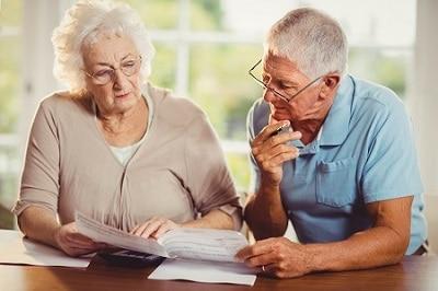 Ein Senioren-Pärchen sitzt vor einem großen Fenster mit Blick auf den Garten und sichtet wichtige Dokumente