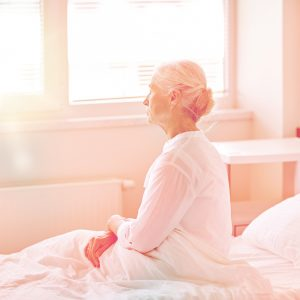 Ältere Dame sitzt in einem hellen Zimmer auf dem Bett und blickt aus dem Fenster.