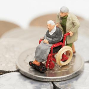 Älterer Mann schiebt alte Frau im Rollstuhl auf einem Stapel Silbermünzen