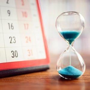 Kalender und Sanduhr mit blauem Sand